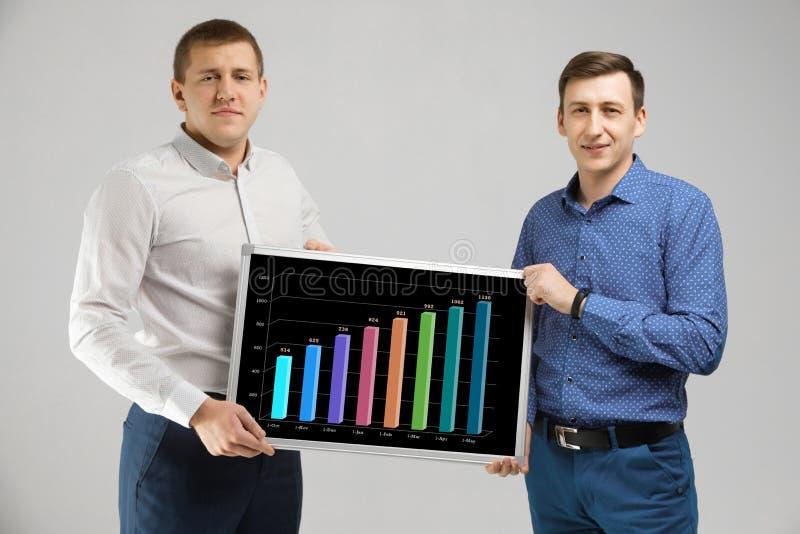 Twee mensen die in die bedrijfskleren een Raad met statistieken houden op witte achtergrond worden geïsoleerd royalty-vrije stock fotografie