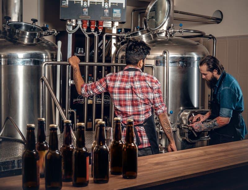 Twee mensen die bier in ambachtmicrobrewery brouwen royalty-vrije stock foto