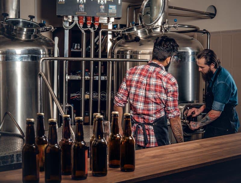 Twee mensen die bier in ambachtmicrobrewery brouwen stock afbeeldingen