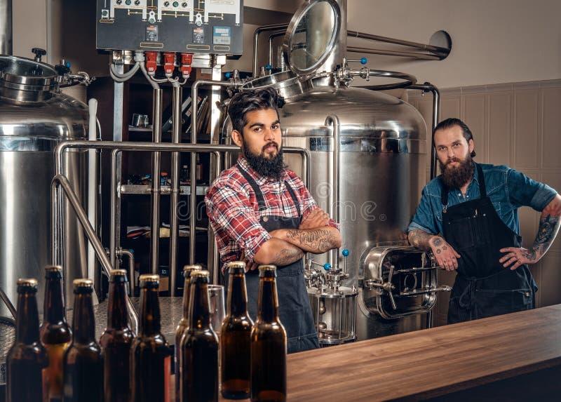 Twee mensen die bier in ambachtmicrobrewery brouwen stock afbeelding