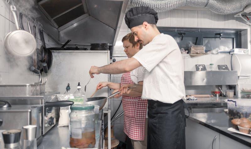 Twee mensen die, commerciële keuken koken royalty-vrije stock fotografie