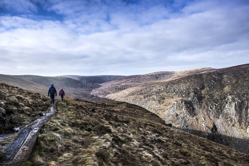Twee mensen die in de heuvels wandelen stock afbeeldingen