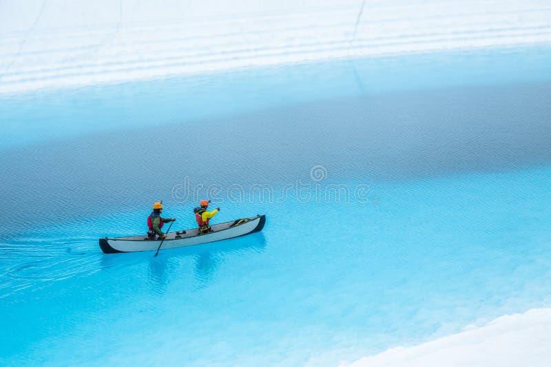 Twee mensen die een kano over een ijzig meer in Alaska paddelen Blauwe pool bovenop een gletsjer in de wildernis royalty-vrije stock afbeelding