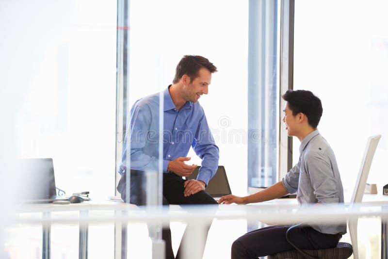 Twee mensen die in een modern bureau spreken stock foto's