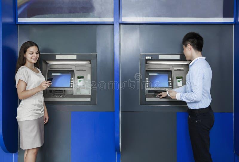 Twee mensen die en geld van ATM bevinden zich terugtrekken stock afbeeldingen