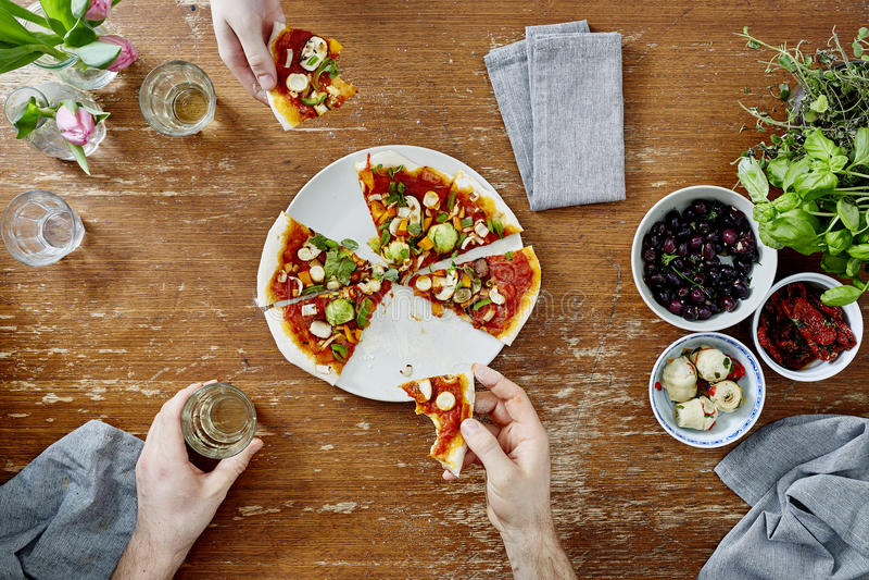 Twee mensen die en pizza delen eten tijdens dinerpartij royalty-vrije stock foto's