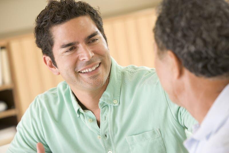 Twee mensen die in en woonkamer zitten die spreekt glimlacht stock foto