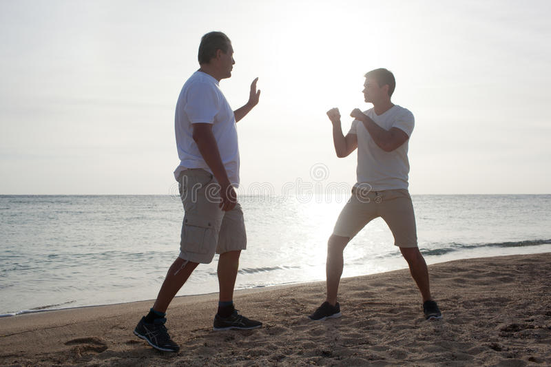 Twee mensen die het in dozen doen opleiding op het strand hebben royalty-vrije stock afbeelding