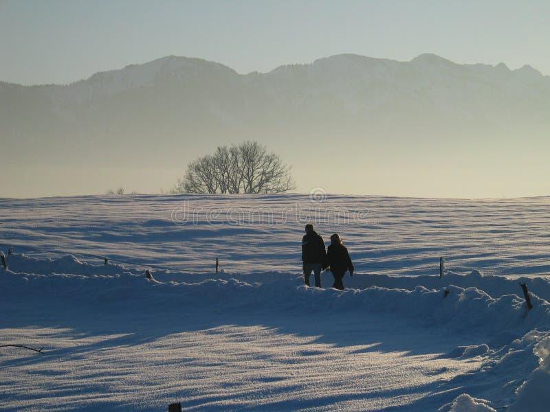 Twee Mensen die in het Eenzame Landschap van de Sneeuw en van de Berg lopen royalty-vrije stock afbeeldingen