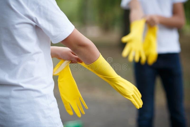 Twee mensen, die latexhandschoen voor het schoonmaken op hand op asfaltachtergrond dragen Vuilnis aan de achterkant royalty-vrije stock afbeeldingen