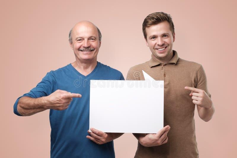 Twee mensen die lege copyspace voor advertentie tonen stock afbeeldingen