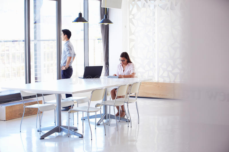 Twee mensen die met digitale tablet in lege vergaderzaal werken stock foto