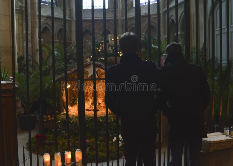 Twee mensen die op een Kerstmiscrèche kijken met Joseph Mary en Jesus in de kerk met bescherming stock fotografie