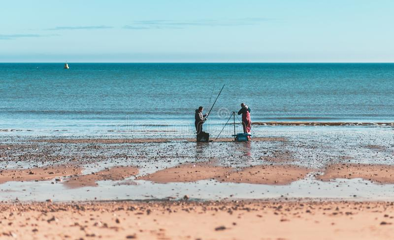 Twee mensen die op Hornsea-Strand vissen stock foto's