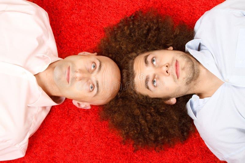 Twee mensen die op rood tapijt liggen royalty-vrije stock foto