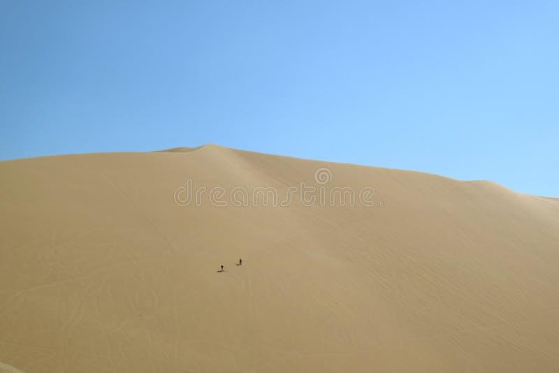 Twee mensen die pret op het enorme zandduin hebben van Huacachina-woestijn, Ica gebied, Peru, Zuid-Amerika stock foto