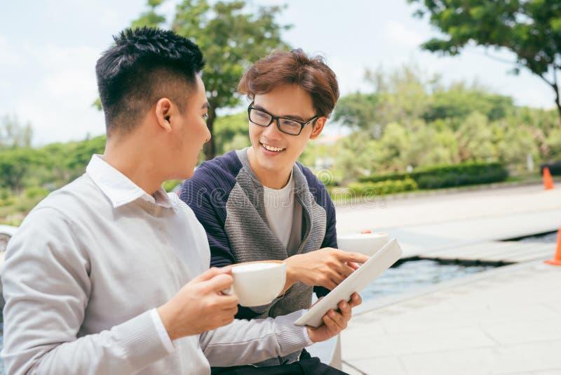 Twee Mensen die Tabletcomputer Internet die, Aziatische Vriendenkerels met behulp van bij Koffie Natuurlijk Licht zitten royalty-vrije stock afbeelding