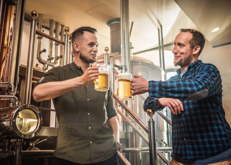 Twee mensen die vers bier in een brouwerij proeven stock foto's