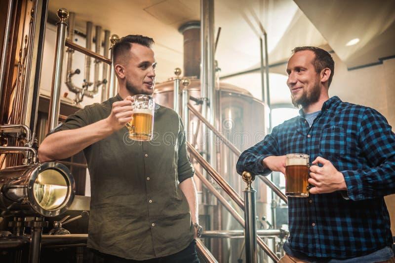 Twee mensen die vers bier in een brouwerij proeven stock afbeelding