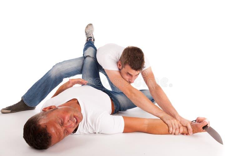 Twee mensen die voor een mes vechten stock afbeeldingen