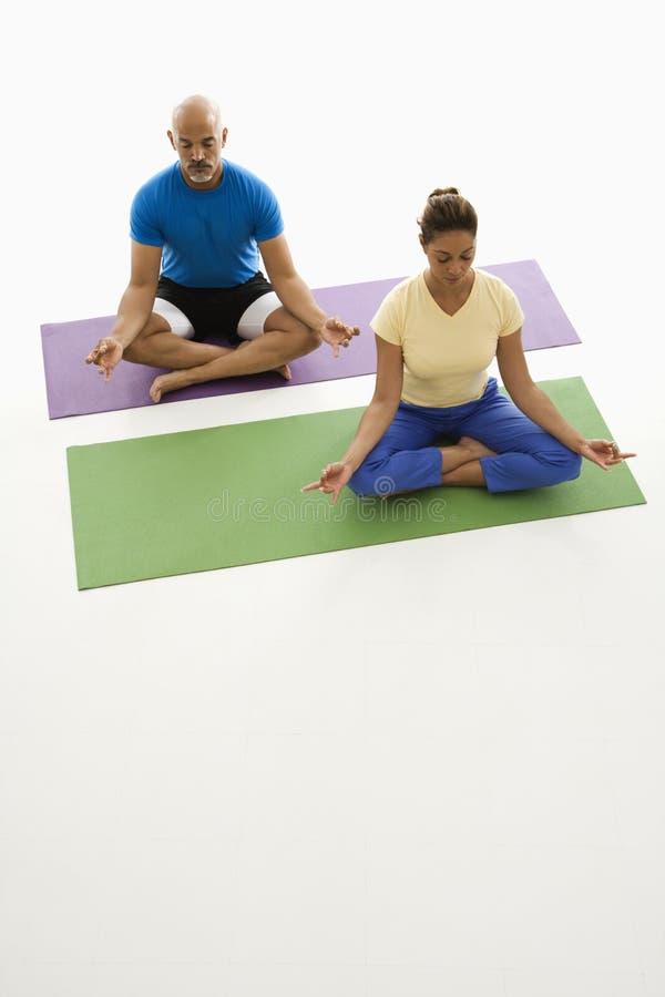 Twee mensen die yoga uitoefenen. stock afbeeldingen
