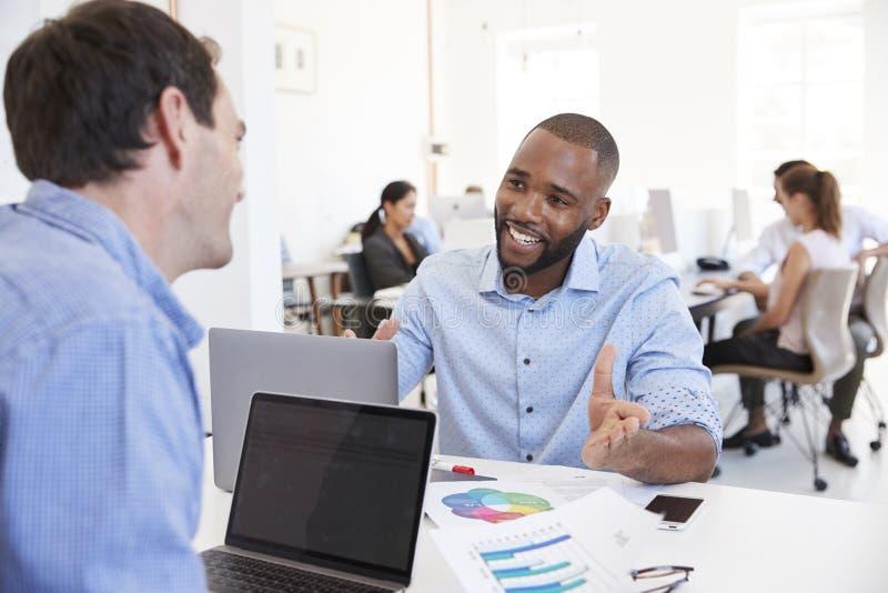 Twee mensen die zaken in een bezig bureau bespreken stock foto