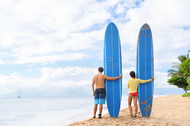 Twee mensen die zich met surfboars bij strand bevinden stock afbeelding