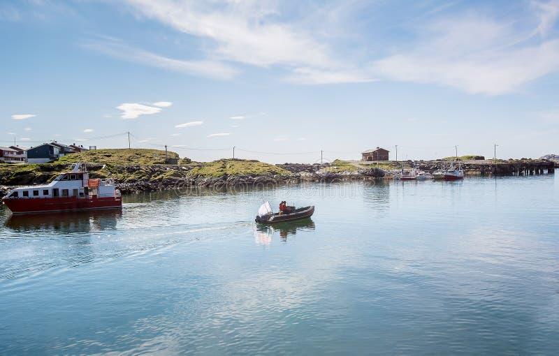Twee mensen in een motorboot die langs de baai varen Overzeese visserij Norw stock afbeeldingen