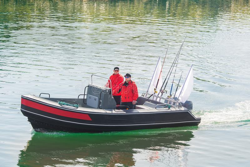 Twee mensen in een motorboot die op het water varen Overzeese visserij Norwa royalty-vrije stock afbeelding