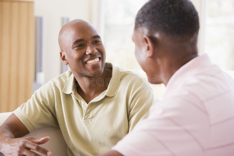 Twee mensen in en woonkamer die spreekt glimlacht stock foto