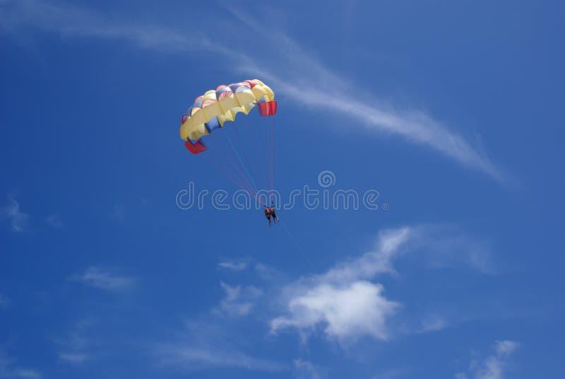 Twee mensen glijden met een valscherm tegen de blauwe hemel Selectieve nadruk royalty-vrije stock fotografie