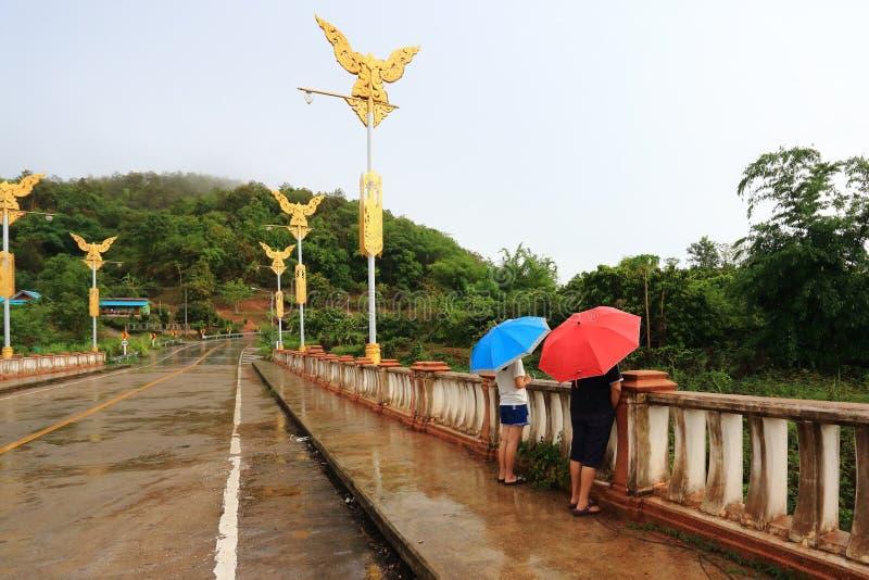 Twee mensen houden paraplu's op de brug stock fotografie
