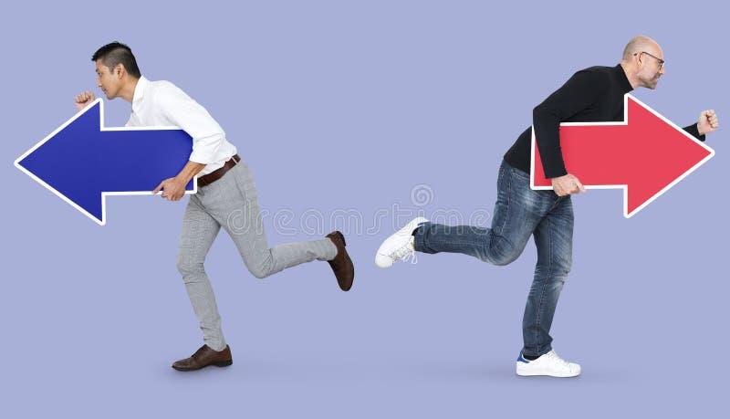 Twee mensen met pijlen en het lopen in tegenovergestelde richtingen royalty-vrije stock afbeeldingen