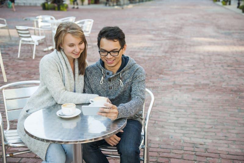 Twee mensen met smartphone in koffie royalty-vrije stock afbeeldingen