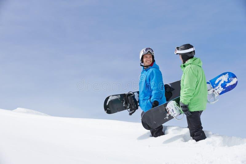 Twee Mensen met Snowboards op Ski Holiday In Mountains royalty-vrije stock fotografie
