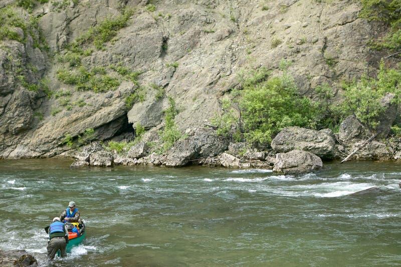 Twee mensen navigeren een rotsachtige rivier in ver Alaska royalty-vrije stock foto