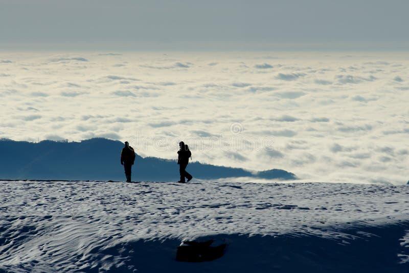 Twee mensen silhouetteren op de sneeuw royalty-vrije stock fotografie