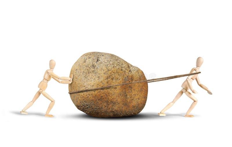 Twee mensen slepen een reusachtige steen stock afbeeldingen