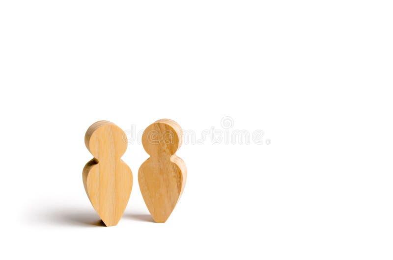 Twee mensen verenigen zich en spreken Drie houten cijfers van mensen leiden een gesprek op een blauwe achtergrond Mededeling, mee royalty-vrije stock afbeeldingen