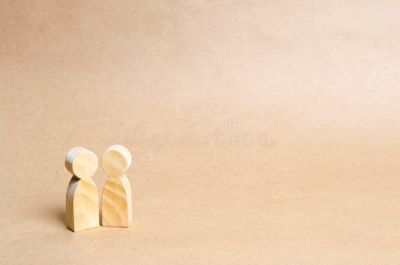 Twee mensen verenigen zich en spreken Twee houten cijfers van mensen leiden een gesprek met een neutrale achtergrond Mededeling royalty-vrije stock fotografie