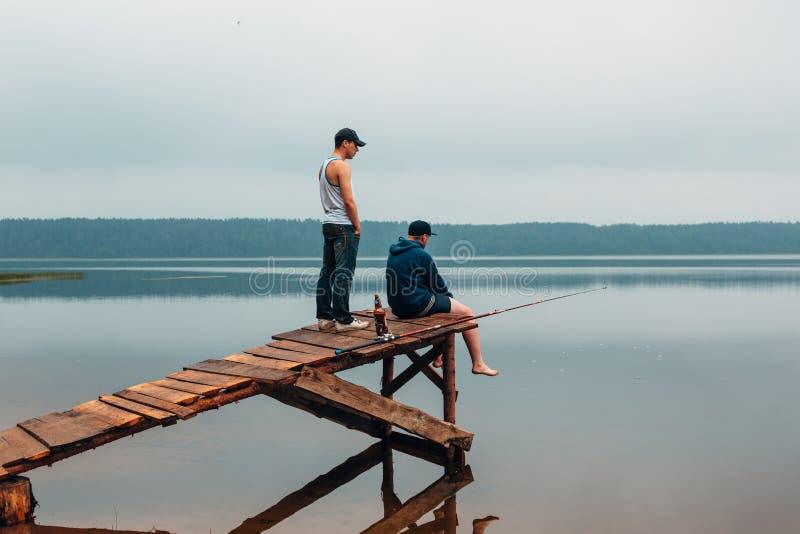 Twee mensen wachten op een houten brug wanneer de vissen bijten stock afbeelding