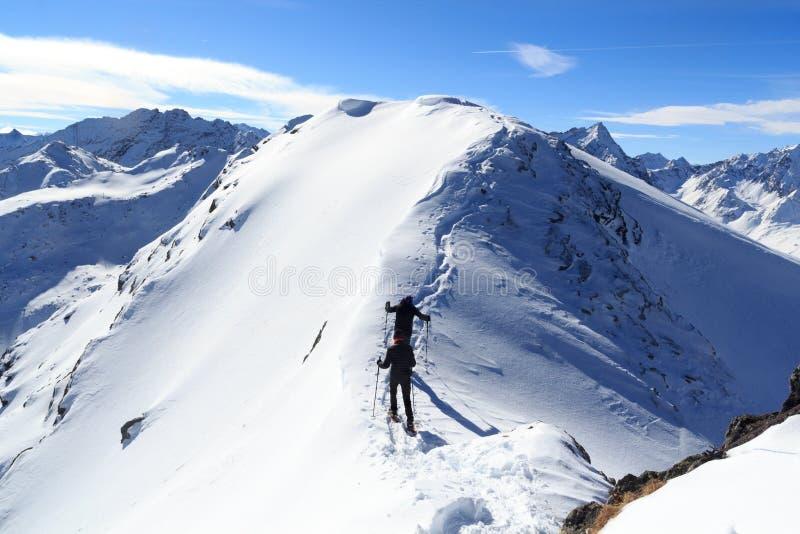 Twee mensensneeuwschoen die op bergsneeuw arete en panorama in Stubai-Alpen wandelen stock afbeelding