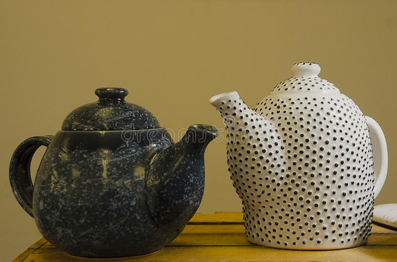 Twee met de hand gemaakte theepotten op een houten plank in de markt Witte ceramische theepot in de zwarte punt Donkere theepot stock afbeeldingen