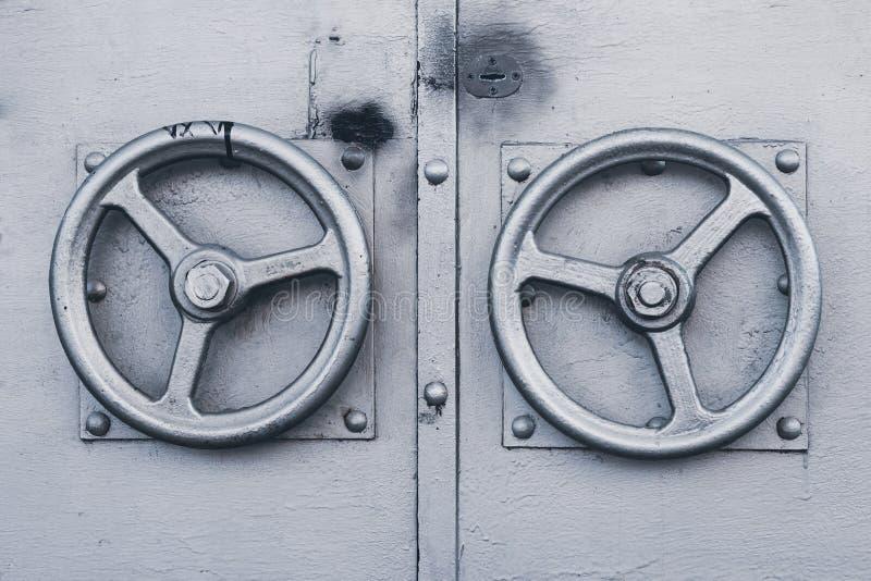 Twee metaal grijze deurhandvatten in de vorm van roerclose-up De metaal grijze deurknop in de vorm van zilverachtig stuurwiel O royalty-vrije stock foto