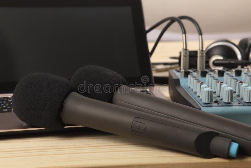 Twee microfoons met laptop en een audiomixer Scherpte op de dichtbijgelegen microfoon Close-up stock afbeelding