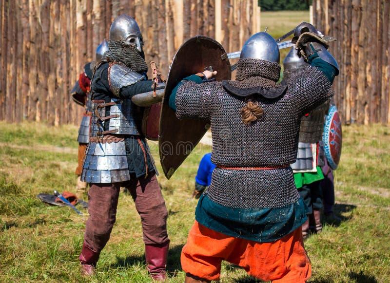 Twee middeleeuwse strijders in pantser vechten royalty-vrije stock afbeeldingen