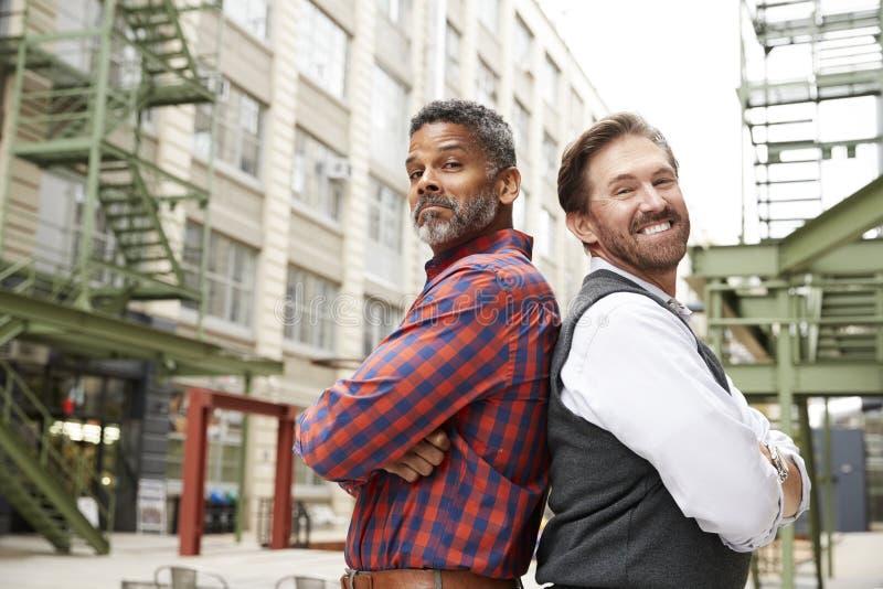 Twee midden oude mensen gaan om buiten werkplaats te steunen achteruit royalty-vrije stock afbeelding
