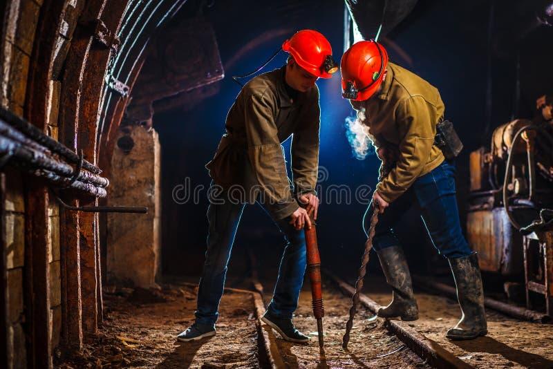 Twee mijnwerkers in de mijn. De ruimte van het exemplaar. hard werken in een steenkoolmijn. Verbonden werknemers in een steenkoolm stock afbeeldingen