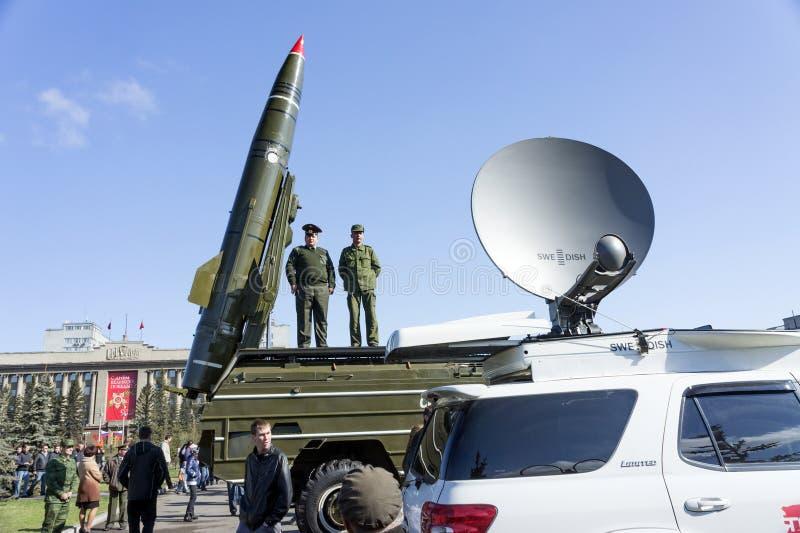Twee militairen bevinden zich op een hulpraket naast een opgeheven raket op het centrale vierkant van Krasnoyarsk stock afbeelding