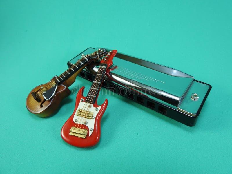 Twee miniatuur elektrische gitaren die tegen een zilveren diatonische harmonika leunen royalty-vrije stock afbeeldingen